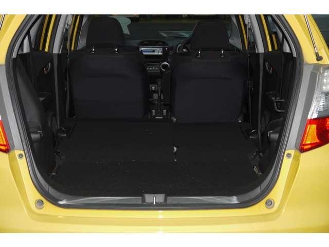 フィットのリアシートは多彩なアレンジ可能。 座面だけ立てかけて 背の高い荷物も 積めます。更にセンタータンクレイアウトなので 座面下には 広いスペースが出現します。人気のシートです。