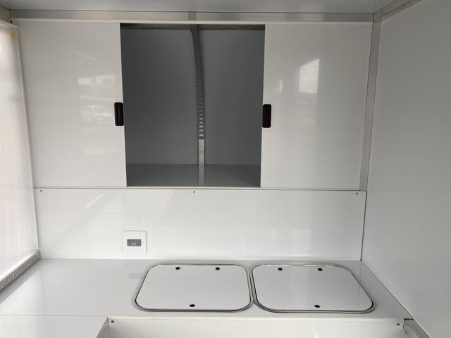 オーバーヘッド部は物置として広いスペースが確保できます。スライド扉付きです。シンクは使用時以外は蓋ができますので作業台としてもお使いできます。