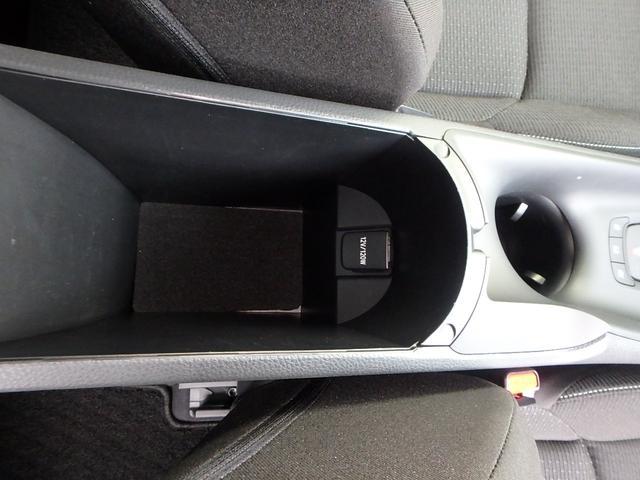 運転手席と助手席の間に有るアームレスト(ひじ掛け)のフタを空けると小物入れになっています。また、12V/120Wのシガーソケットも有りますので携帯電話の充電等にも便利です。