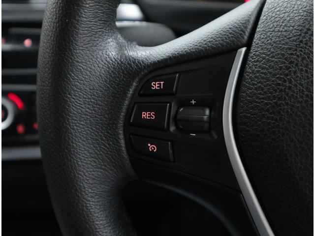マルチファンクションスイッチ付きの革巻きステアリング。左側は、クルーズコントロールスイッチです。