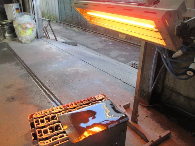 塗装したパーツの乾燥作業です。赤外線乾燥機を使いホコリが乗る前に乾燥させます。