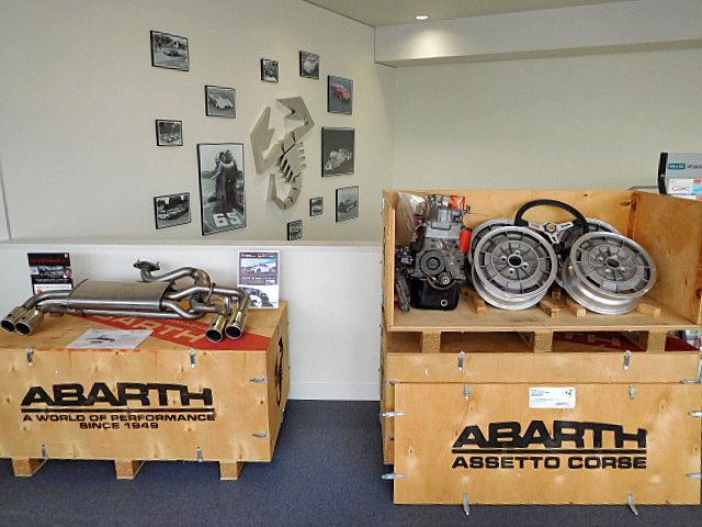 歴代のアバルトのパネルやヒストリックアバルトのパーツを展示したガレージのようなショールーム